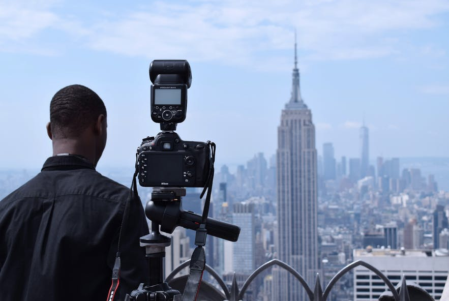 A man dressed in back has his back to the camera, standing next to a camera and flash system, pointing towards the skyline of New York City