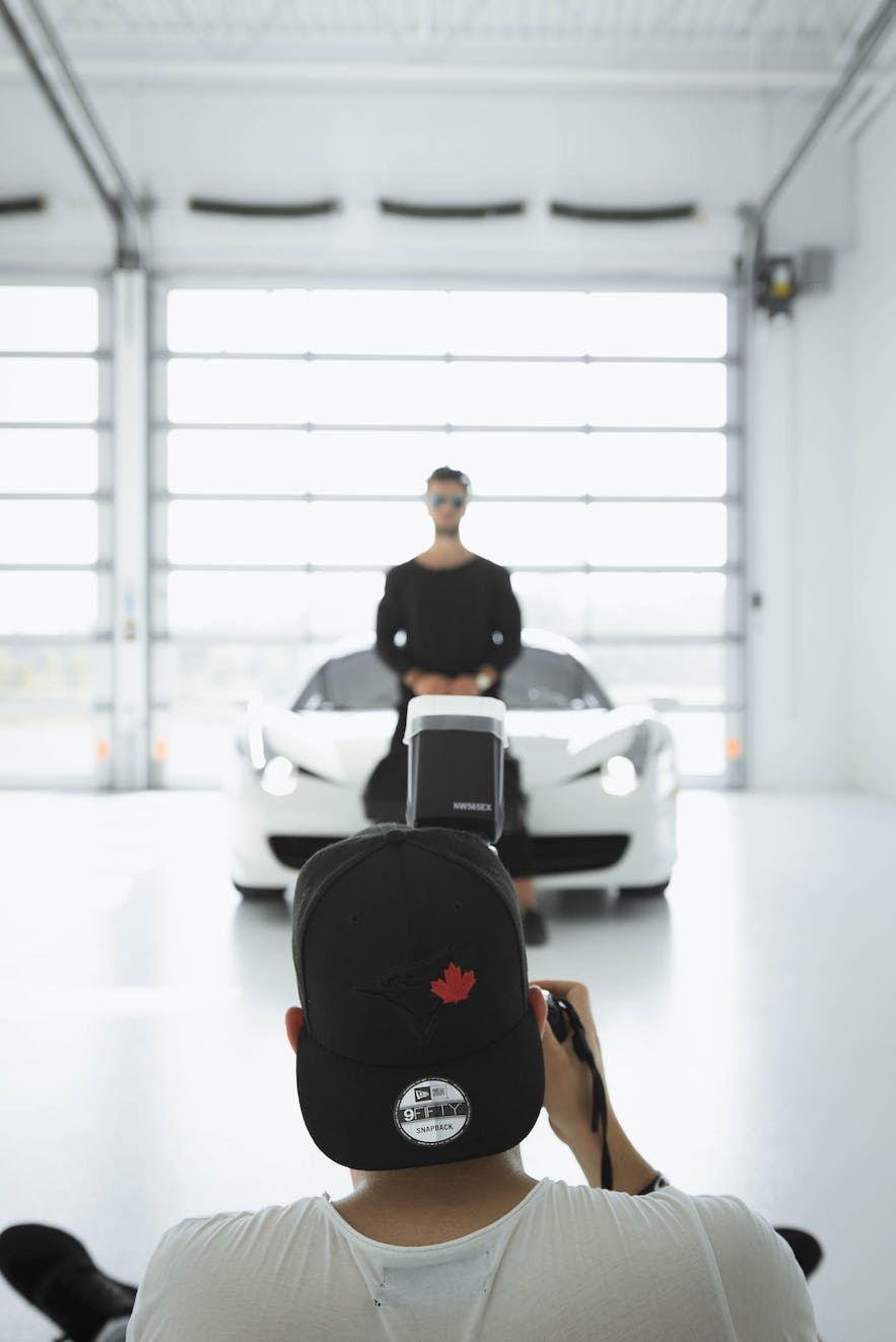 A photographer in a black cap captures a man and white sports car in a studio environment