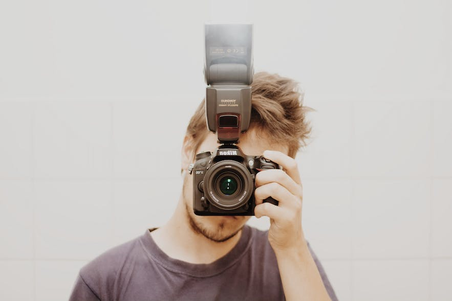 Guy holding a camera in front of his face