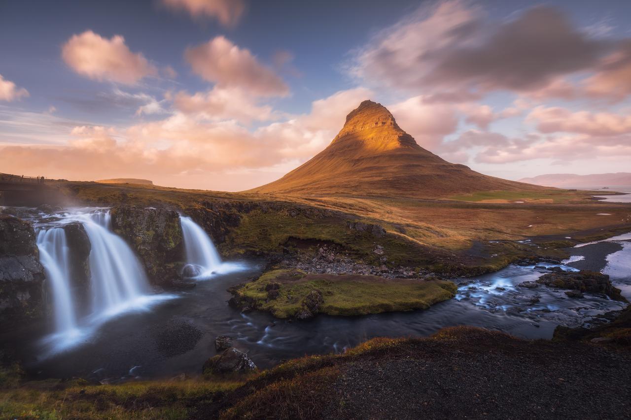 Un encantador arroyo atraviesa un campo de musgo desde un pico de montaña irregular en la península de Snæfellsnes.