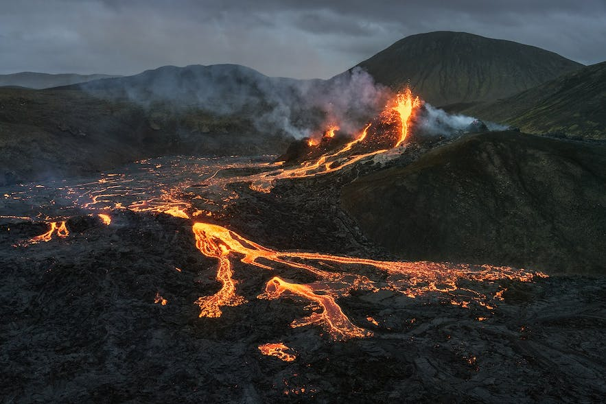 Flames sputter and lava rivers run from the Geldingadalur eruption site in Iceland.