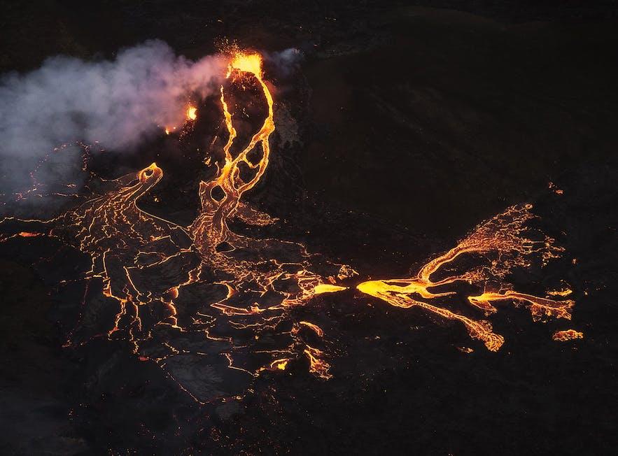 The lava of Geldingadalur glows on the dark, winter night in Iceland.